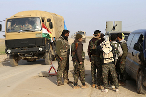 Military vehicles pass as YPG and PKK fighters man a checkpoint on a highway connecting the Iraqi-Syrian border town of Rabia and the town of Snuny north of Mount Sinjar
